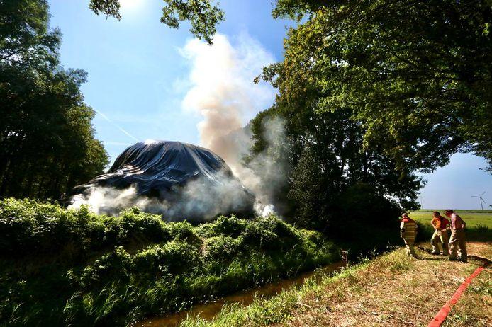 De brandweer is druk in de weer bij een brandende hooibult bij Nagele.