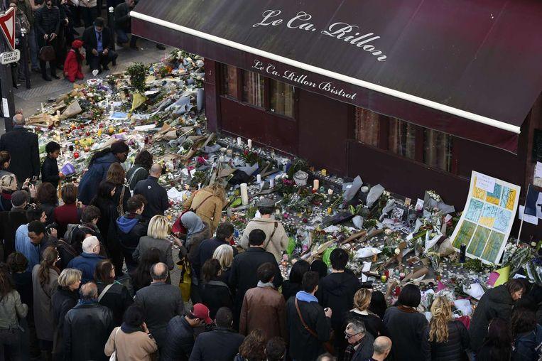 Mensen leggen bloemen neer bij restaurant Le Carillon. Beeld afp