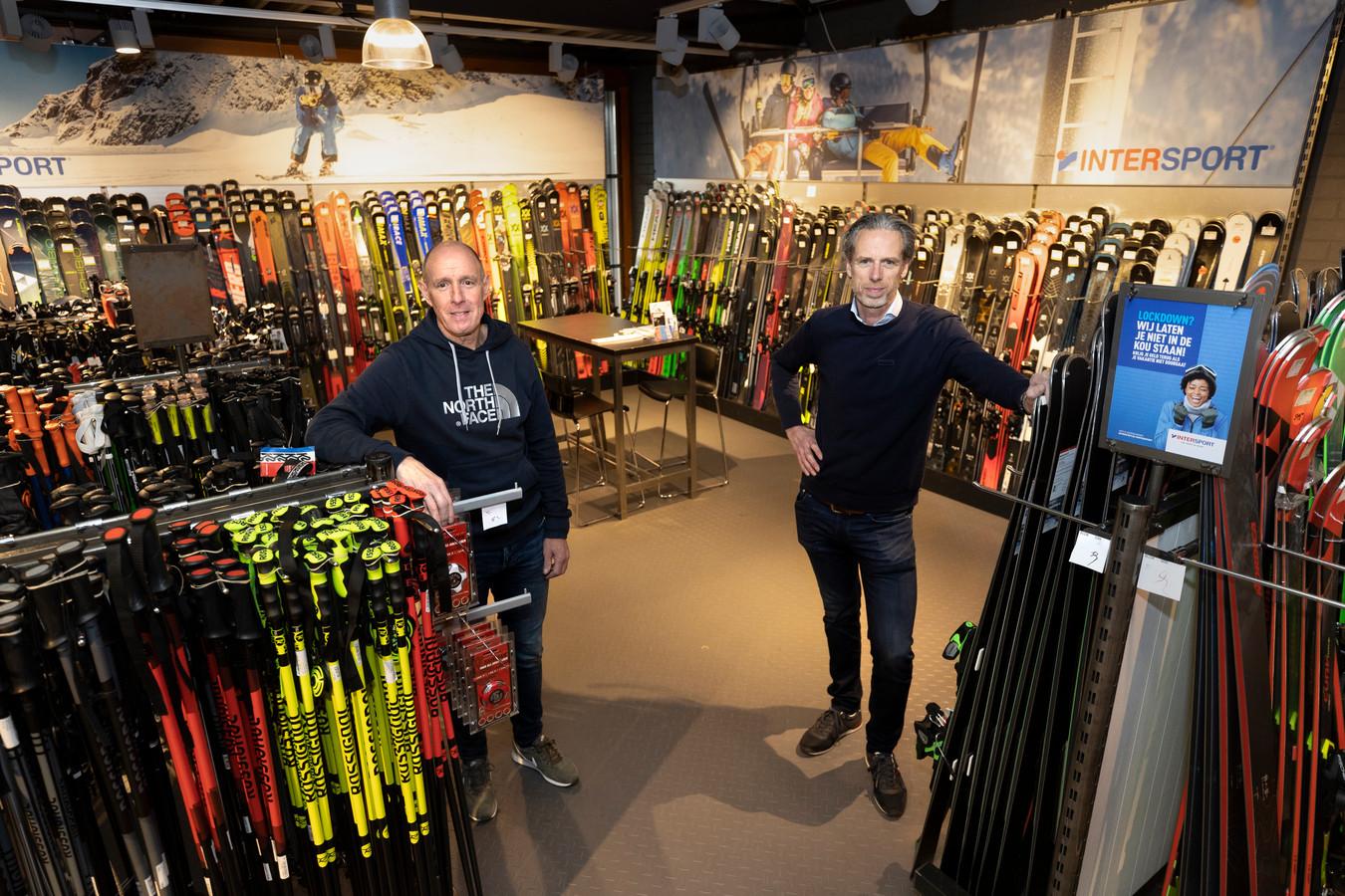 Geert van der Velden (links) en Johan van den Broek van sportwinkel Intersport voor een wand vol onverkoopbare ski's.