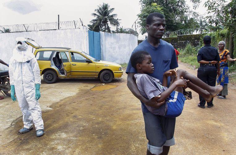 Een man draagt zijn zieke broer in Monrovia in Liberia naar een lokaal hospitaal. Beeld EPA