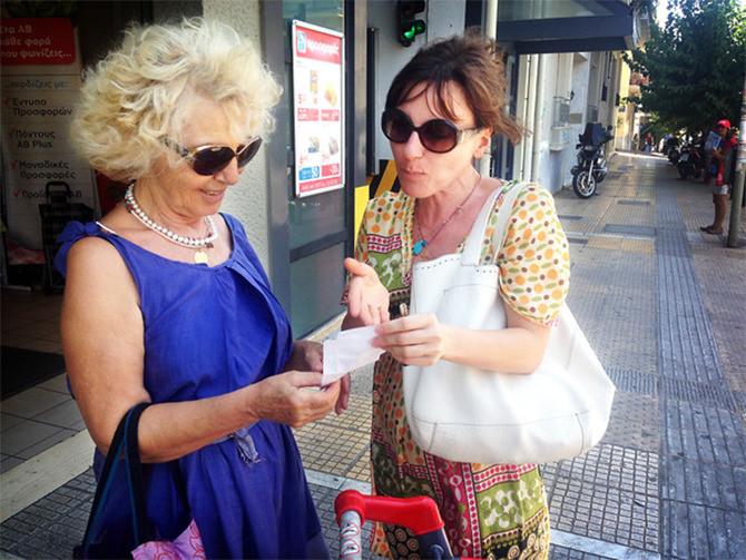 Ioanna Theodorakopoulou en haar dochter Maria bestuderen de btw op de supermarktbon.