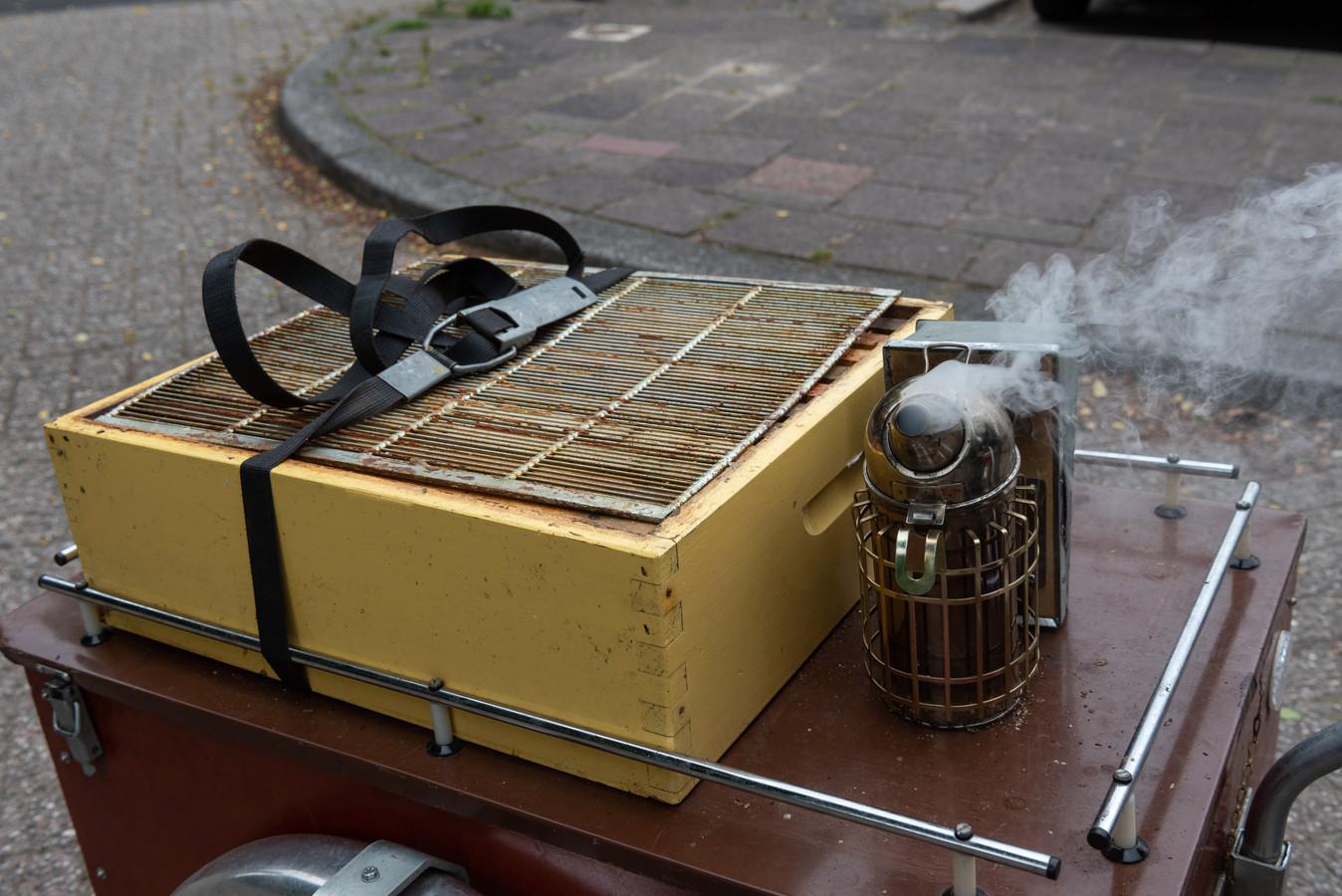 Een extra honingkamer mee op de fietskar om op het bijenvolk te zetten. De roker met tabak staat voor gebruik gereed.