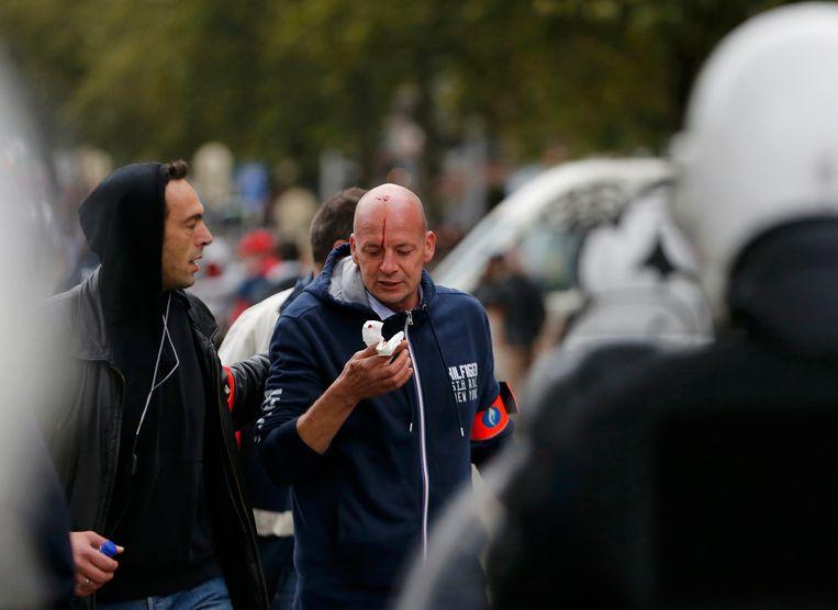 Een politieman in burger raakte gewond bij de rellen met betogers. Beeld REUTERS