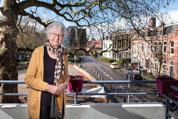 Bep van der Veer op het balkon van haar flat in de Schimmelpenninckstraat. Eerder woonde ze rechts, waar de vuilcontainers staan.