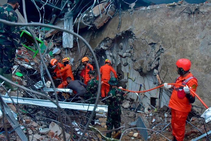 Reddingswerkers in een ingestort gebouw.