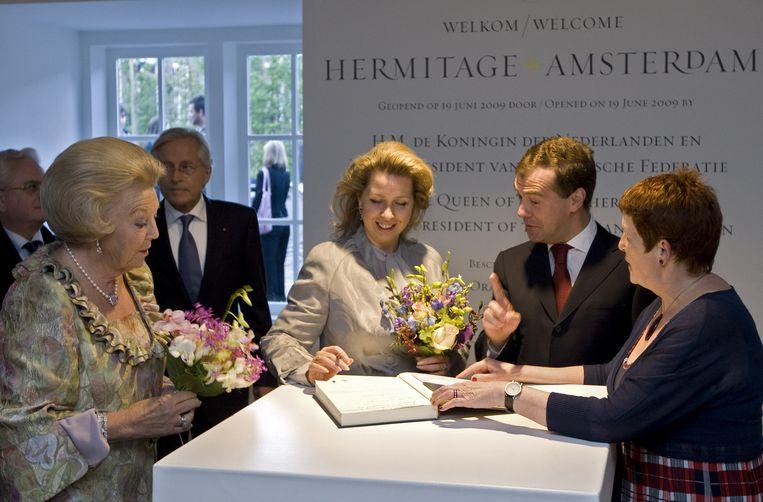 Svetalana Medvedeva tekent vrijdagavond het gastenboek bij de opening van museum de Hermitage in Amsterdam, met de Russische president Medvedev en koningin Beatrix. Foto ANP Beeld