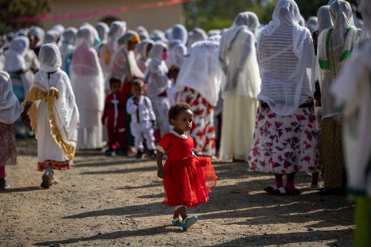 In Mekele, de hoofdstad van Tigray, wandelt een meisje langs een groep volwassenen die in de openlucht een kerkdienst bijwonen. Na zes maanden van geweld in de noordelijke provincie van Ethiopië is er nog altijd geen zicht op vrede.  Beeld AP