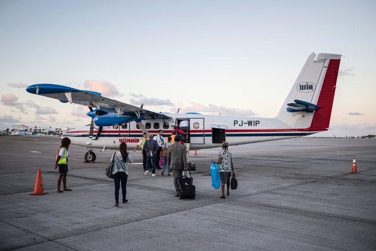 Passagiers lopen naar een vliegtuig van Winair op het vliegveld Princess Juliana International Airport op Sint Maarten.  Beeld Hollandse Hoogte /  ANP