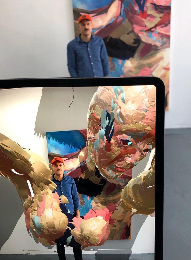 Dennis Rudolph met de digitaal geschilderde figuren in zijn atelier. Beeld