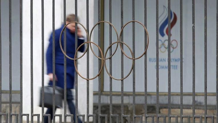Een man loopt langs het hoofdkwartier van het Russisch Olympisch comité. Beeld EPA