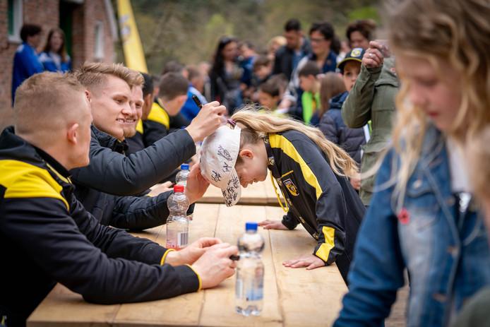 Vitesse-speler Martin Ødegaard zet ook zijn handtekening op het petje van een jonge fan. Marcus Thelander (links) kijkt of het goed gaat.