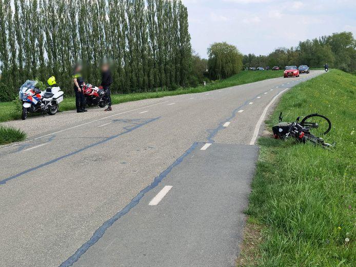 Een van de fietsen ligt in de berm van de Grebbedijk nadat twee wielrijders door een motorrijder van de sokken zijn gereden.