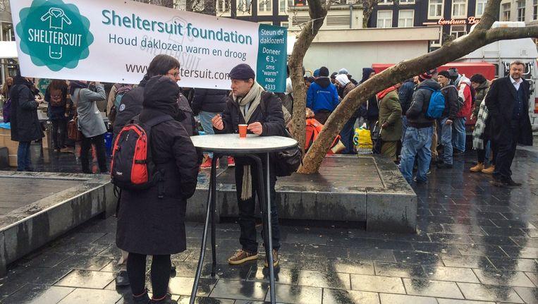 De sheltersuits worden uitgedeeld aan de daklozen op het Rembrandtplein. Beeld Eva Plevier
