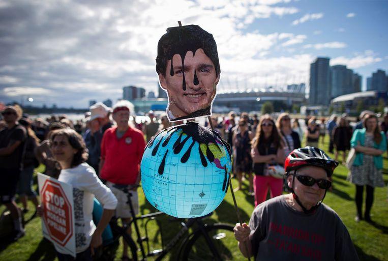 Een demonstrant houdt een foto op van een met olie besmeurde Justin Trudeau tijdens protesten tegen de uitbreiding van de Trans Mountain-pijpleiding in Vancouver. Beeld AP