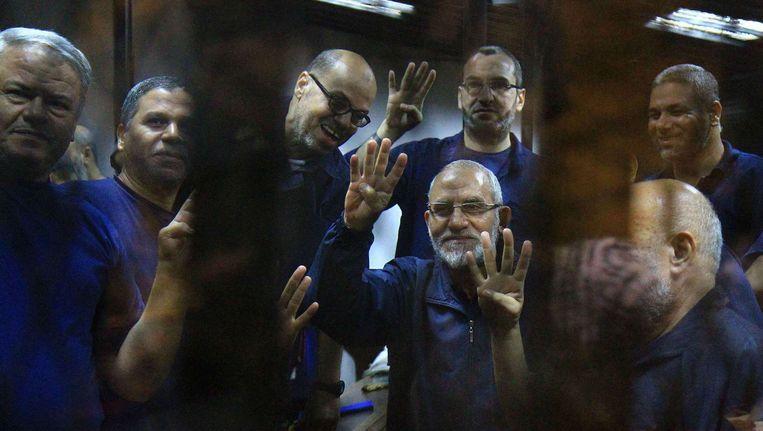 Enkele kopstukken van de Moslimbroederschap, waaronder leider Mohamed Badie (midden), op de beklaagdenbank in Caïro. Beeld BELGA