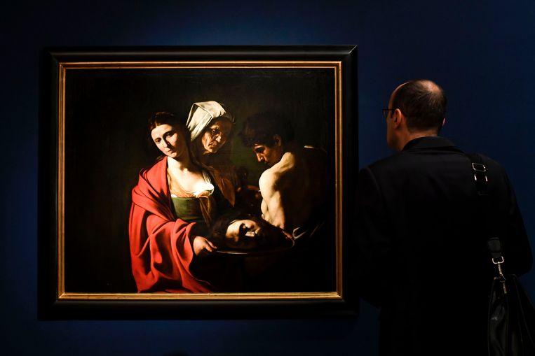Een man bekijkt het doek 'Salome met het Hoofd van Johannes de Doper' in het Scuderie del Quirinale in Rome.  Beeld AFP
