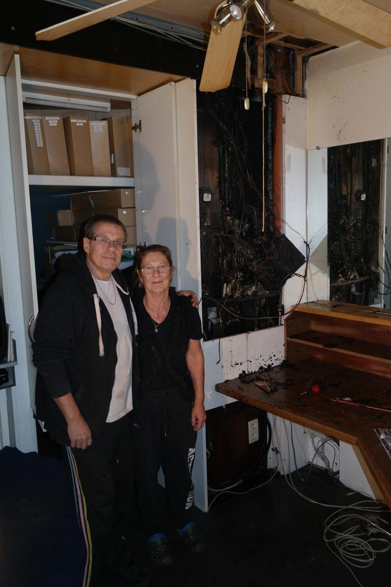 Eigenaars Carlos De Clercq en Carine De Laender bij de zekeringkast waar de brand ontstond.