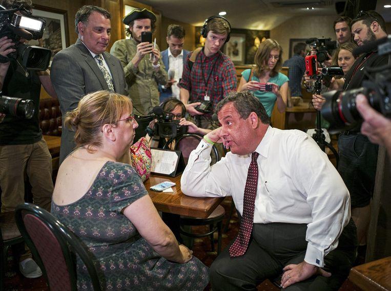 Christie praat in een restaurant in New Hampshire met een klant. Slechts een minderheid van de bewoners van zijn staat New Jersey, 33 procent, vindt dat hij zijn werk goed doet als gouverneur. Beeld EPA