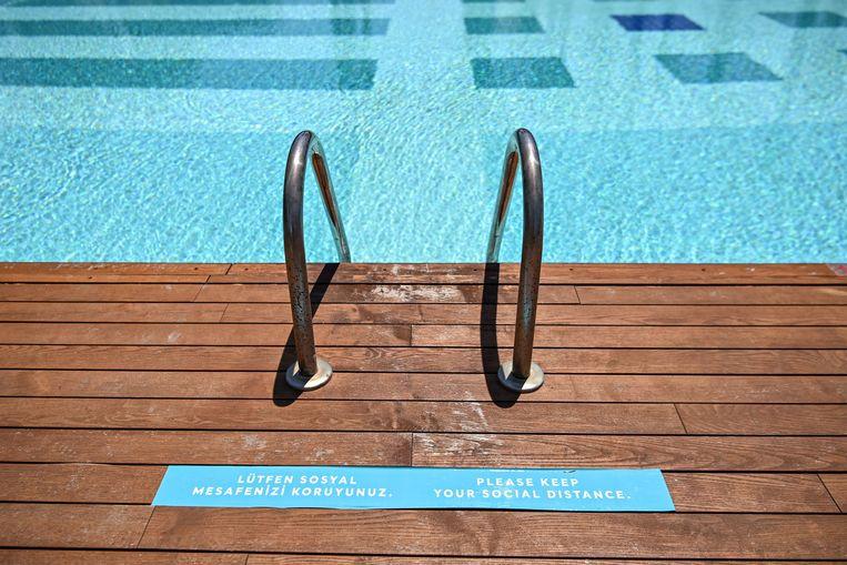 Hou afstand, lees je voor je in het zwembad gaat.  Beeld AFP