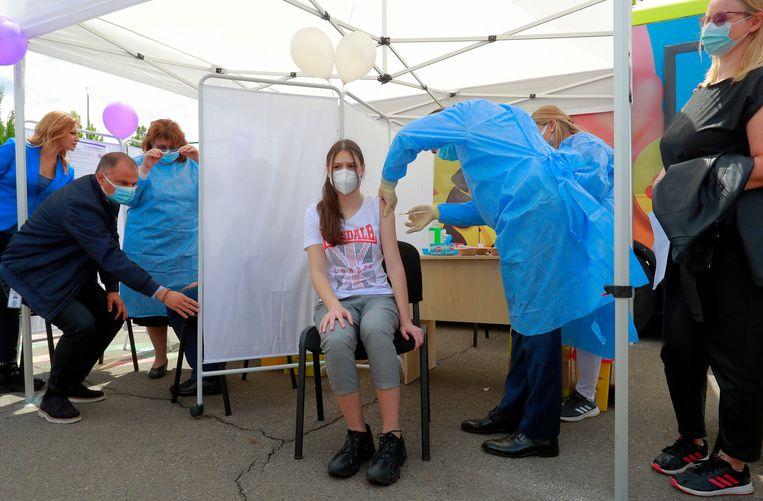 Een meisje van 14 jaar wordt in Roemenië ingeënt. Beeld EPA