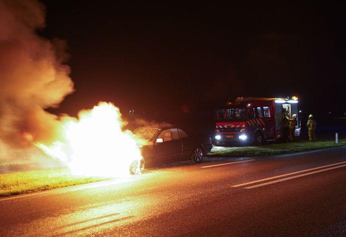 De vlammen slaan uit de auto in Didam.