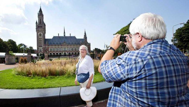 Een toerist maakt een foto van het Vredespaleis, daags voor de viering van het 100-jarig bestaan ervan. Beeld anp