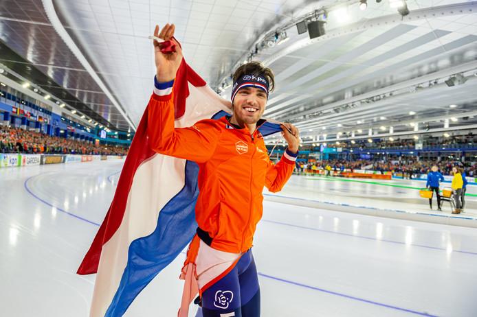 Patrick Roest maakt een ereronde met de vlag nadat hij Europees kampioen is geworden op de 5000 meter.