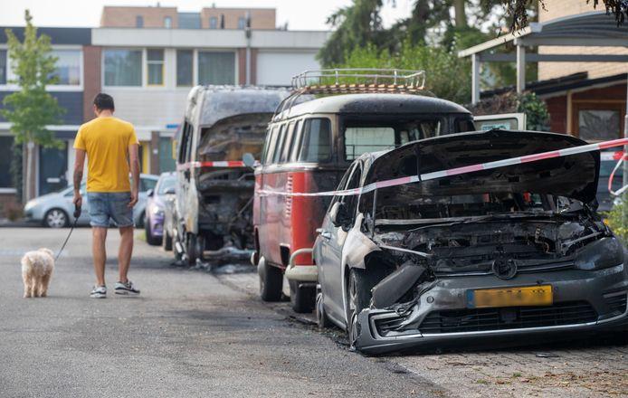 Een buurtbewoner loopt met zijn hondje over de weg langs een rij door brandschade gemerkte auto's: de stoep is met linten versperd.