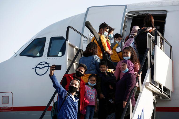Vluchtelingen die verbleven in het door brand verwoeste kamp in Moria, stappen op het vliegtuig naar Duitsland. Beeld EPA