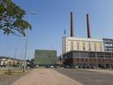 Links de biomassacentrale van Ennatuurlijk op Strijp-T in Eindhoven; naast de voormalige energiecentrale van Philips (met de schoorstenen) die nu in gebruik is als kantoorgebouw.