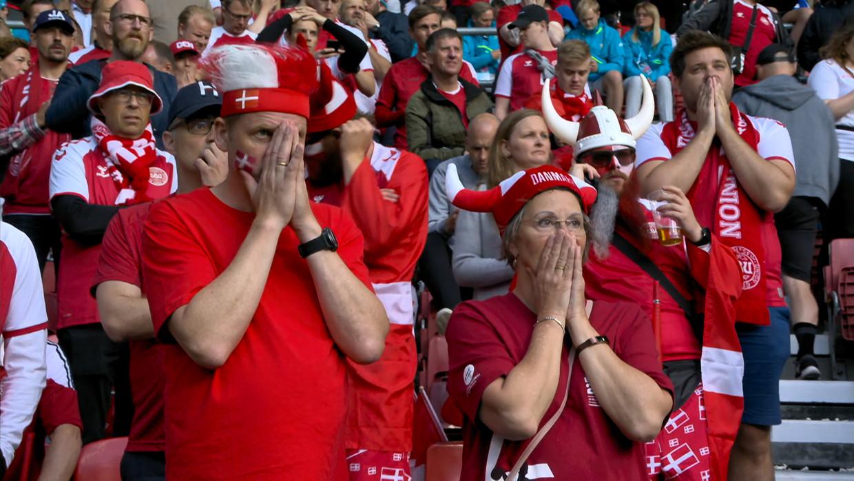 Deense fans reageren geschokt wanneer Christian Eriksen ineens op het veld in elkaar zakt. Beeld VRT