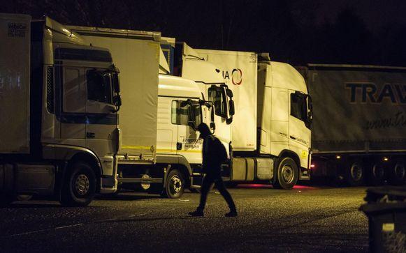 Een nachtelijk beeld op de snelwegparking in Groot-Bijgaarden, waar vluchtelingen tussen de vrachtwagens lopen. Ze zoeken er die naar Engeland gaan en proberen zich dan tussen de lading te verstoppen.