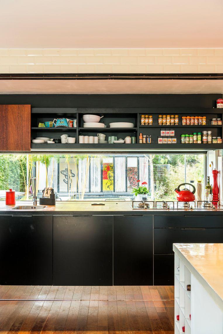 De spiegelende plinten onder de keukenkasten laten de vloer optisch doorlopen en zorgen zo voor extra ruimtegevoel. Beeld Luc Roymans