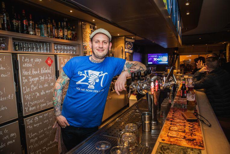 Mich Vynckier in zijn café De Zot, met beker-T-shirt.