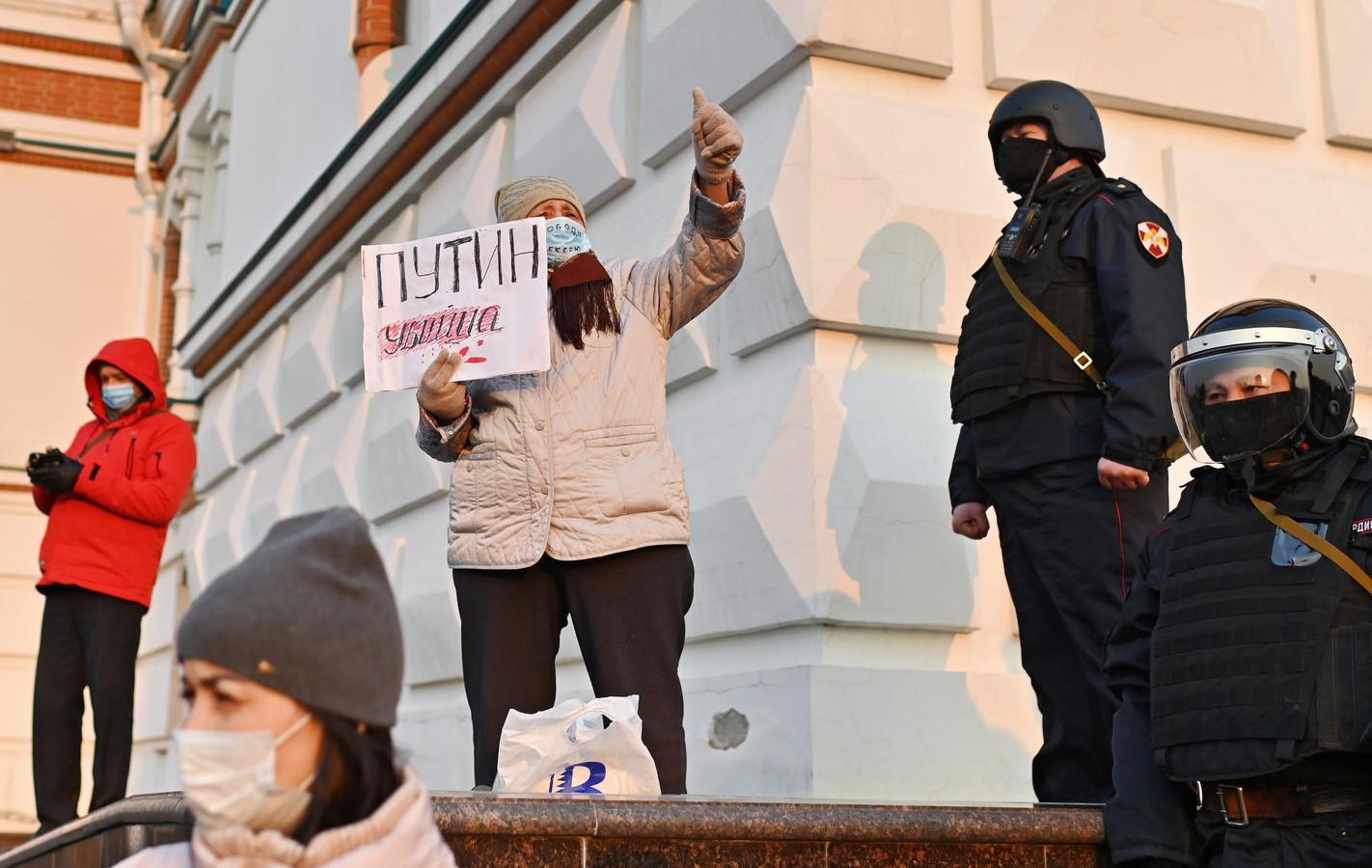"""Een Navalny-aanhangster in Omsk houdt een bord omhoog met de tekst: """"Poetin is een moordenaar""""."""