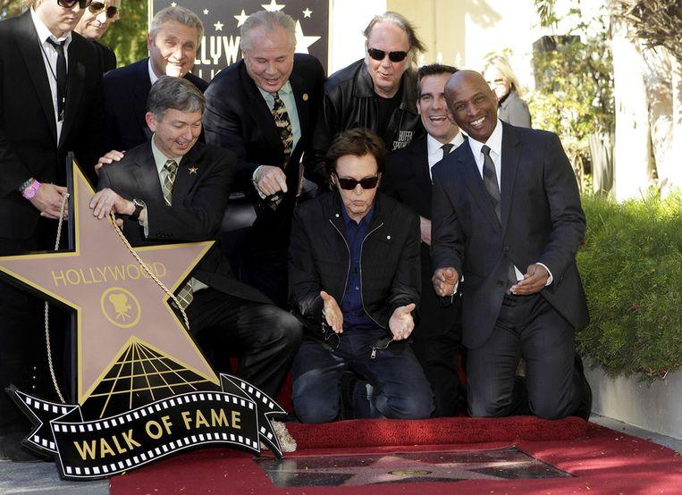 Paul Mc Cartney, vergezeld door onder meer Neil Young (direct achter hem in beeld), bekijkt zijn ster op de Wall of Fame. Beeld ap