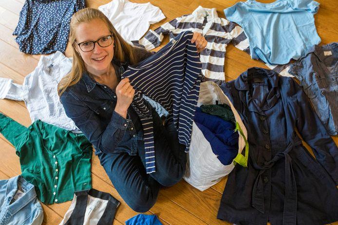 Saskia Vermeer tussen kleren die ze niet meer draagt en die ze in de tas doet om door te geven aan anderen.