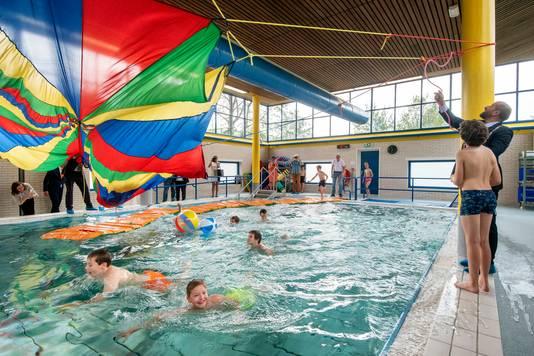 Burgemeester Ahmed Marcouch (r) en leerlingen van mytylschool De Lichtenbeek openen het vernieuwde zwembad van Bio Vakantieoord in Arnhem.