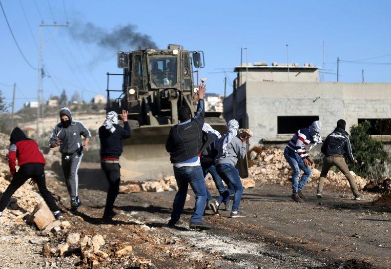 Palestijnen gooien stenen naar een Israëlische bulldozer op de Westelijke Jordaanoever.  Beeld REUTERS