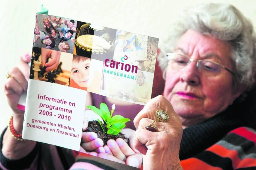 Oudere bekijkt activiteitenblad van Carion. foto: Marc Pluim