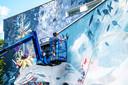 Kunstenaar Collin van der Sluijs brengt de muurschildering aan, hij krijgt volgend jaar een compensatieopdracht.