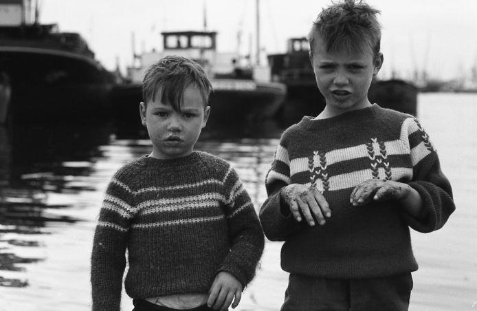 Twee jongens in trui bij de Maashaven, in 1961. Bij de meeste foto's heeft Tjemmes de gefotografeerde personen later kunnen achterhalen, maar bij dit duo tast hij nog in het duister. Wie weet wie deze jongens zijn en wat er van hen terecht is gekomen? Zijn het nu brave huisvaders? Stuur uw suggesties naar rd.reageren@ad.nl