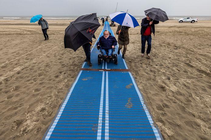 Rick Brink, voormalig minister van Gehandicaptenzaken, neemt de eerste strandmat officieel in gebruik.