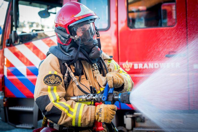 Brandweerman bezig met bluswerkzaamheden. Beeld ANP