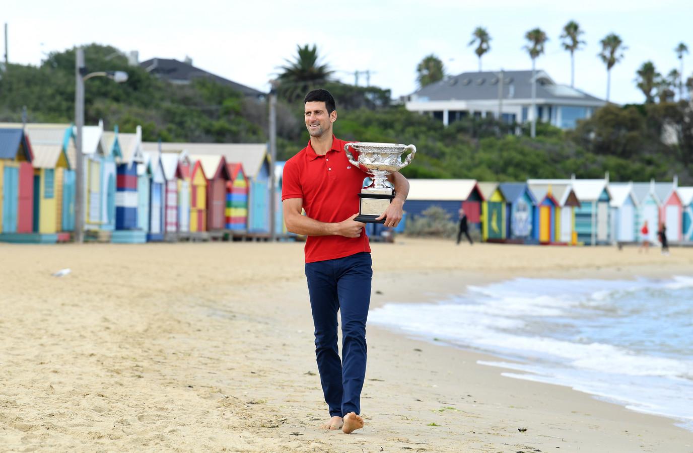 Novak Djokovic loopt een dag na zijn zege in de Australian Open met de Norman Brookes Challenge Cup over het strand van Brighton Beach in Melbourne.