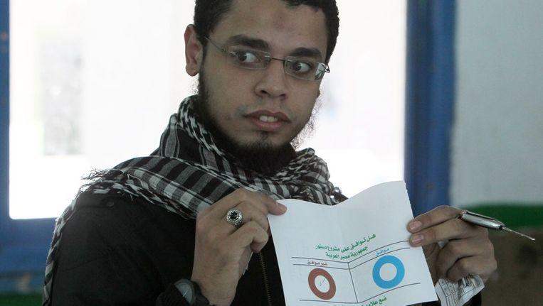 Een Egyptische man toont zijn stembiljet voor het referendum over de nieuwe grondwet; rood is nee, blauw is ja Beeld ANP