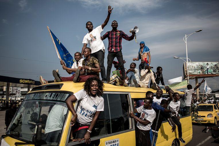 Aanhangers van Martin Fayulu, zakenman en gezamenlijke presidentskandidaat van vijf oppositiepartijen, rijden achter diens konvooi aan op weg van het vliegveld naar het centrum van Kinshasa. Beeld AFP