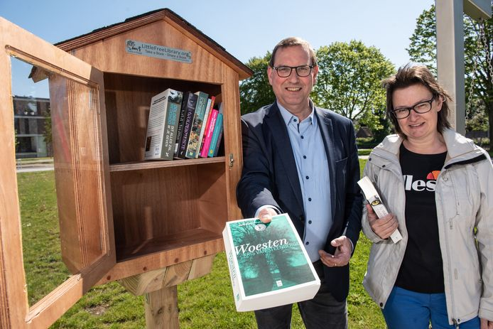 Cultuurschepen Stefaan Vercamer (CD&V) en bibliothecaris Els De Vos bij het boekenruilkastje aan de Schelde.