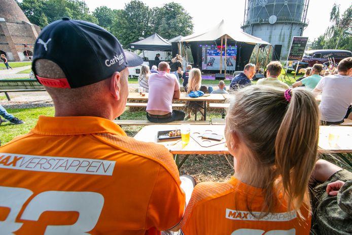 """Rudy Klok kijkt met zijn gezin, in oranje tenue naar de verrichtingen van de Formule 1-coureurs op het grote beeldscherm. ,,Gewoon genieten is het, het kan weer. Maar toch blijft het ook raar. Wie zegt dat ik geen corona heb, al heb ik de app."""""""