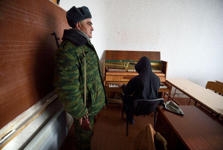 Igor Mychajlysjyn stemt als krijsgevangene op eigen verzoek de piano van de bibliotheek van Ilovaisk, in december 2014.  Beeld Hollandse Hoogte / AFP